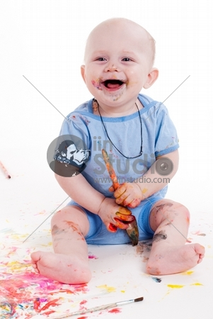 Full-length portrait of a cheerful grimy kid. playing with paint. on a white studio background.