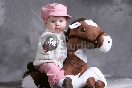 Beautiful Caucasian Baby Girl in a Pink Hat on a toy Horse