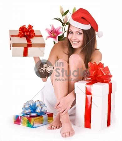 Christmas girl in santa hat, flower, gift box in spa.
