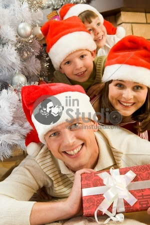 Portrait of happy man in Santa cap holding giftbox with his family on background
