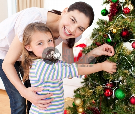 Happy mother and her daughter decorating a Christmas tree