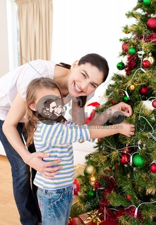 Mother and her daughter decorating a Christmas tree at home