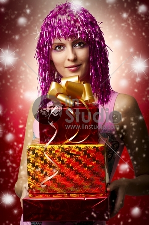 Glamour portrait of christmas happy woman model who holding three red, yellow boxes with gifts or christmas presents in hands. christmas presents