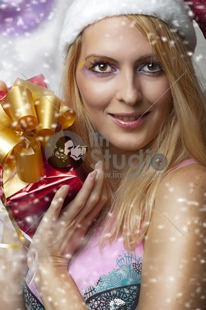 Christmas concept. Beauty portrait happy woman model holding gift in hands and smile about christmas tree in santa claus hat and with bright make-up
