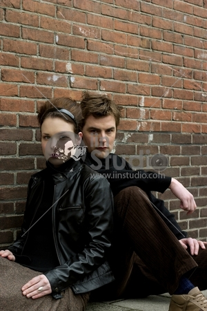 Fashion Models posing in front of brick wall