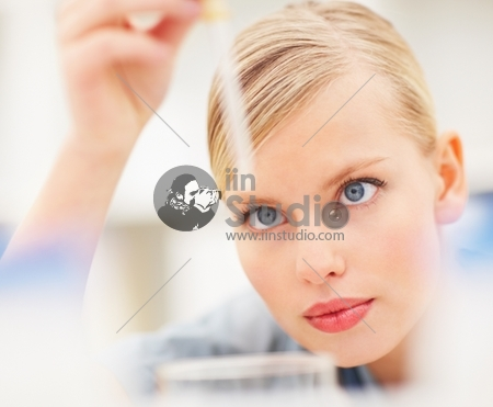 Closeup Of Beautiful Young Female Doctor Using A Dropper