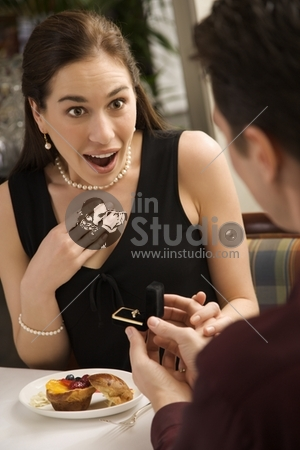 Mid adult Caucasian man proposing marriage to surprised woman at a restaurant.