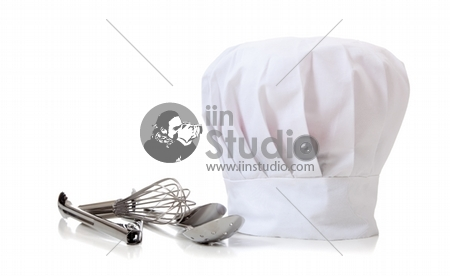 A chefs hat and utensils on a white background