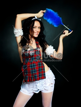 sexy brunette maid with a brush against black background