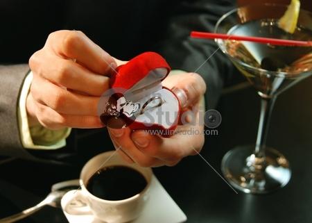 Hand holding wedding ring proposing