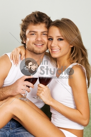 Cheerful young couple drinking wine on green sofa