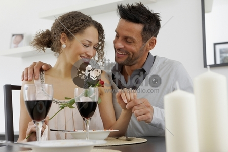 Portrait Of Romantic Young Couple At Dinning Table With Woman Holding Rose And Looking At The Engagement Ring