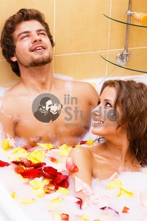 Beautiful young couple enjoying a bath with rose petals