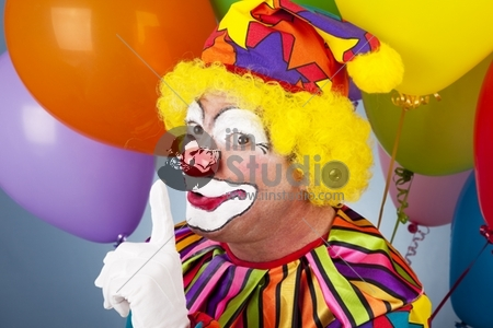 A colorful clown putting his finger to his lips so you will be quiet.