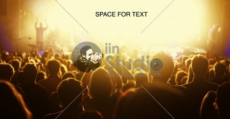 Orange-toned image of audience at live concert cheering with bright light at stage area as free space for text.