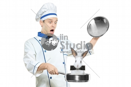A surprised chef holding a frying pan with a rabbit in it isolated on white background