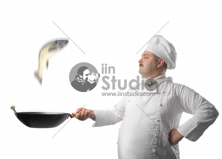 Man cooking a fish in a pan