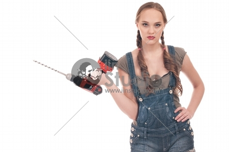 Young playful woman in jeans coverall holding orange drill with huge auger