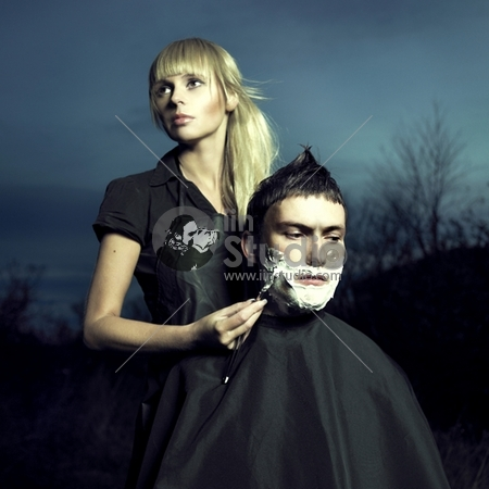 Beautiful woman barber shaves a courageous man. Surreal picture