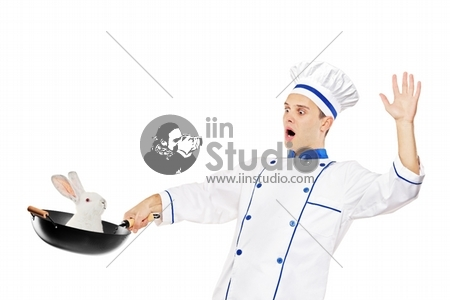 A surprised chef holding a wok with a rabbit in it isolated on white background