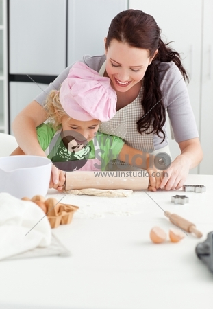 Beautiful mother and her cute daughter using a rolling pin together in the kitchen