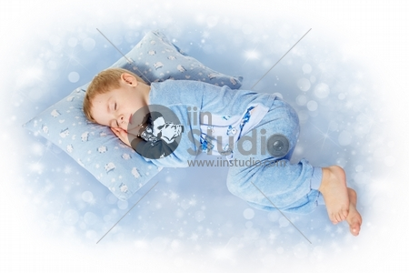 Child sleeping on pillow in sleepwear. Magic blue background