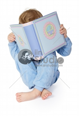 Little child reading book. Hiding behind book. Legs crossed. Over white background.