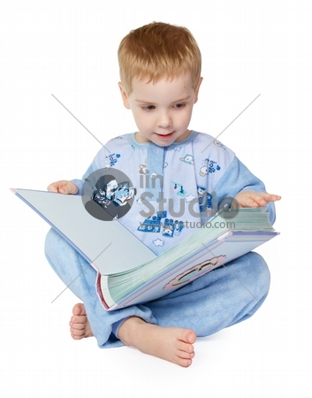 Little child reading big book. Legs crossed. Over white background.