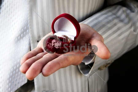 Wedding rings placed in red casket on the hand of young man