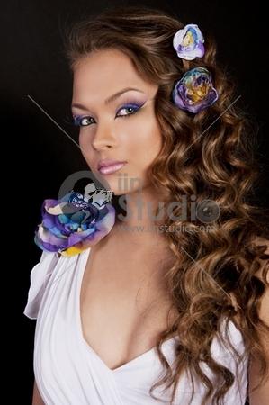 Pretty brunette young woman with creative makeup and flower in curly hair on white background