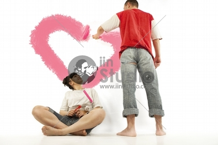 Young couple of workers painting heart on a wall with roller