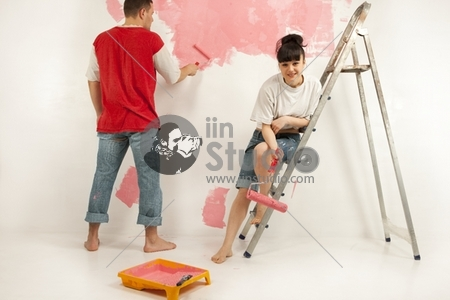 Cheerful young couple of workers preparing to painting a wall