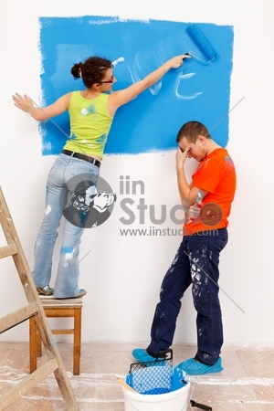 Girl repainting her love message in the wall of a renovated house