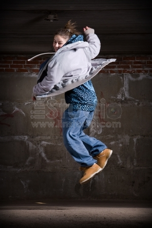 Hip hop girl dancing in modern style over urban grey brick wall