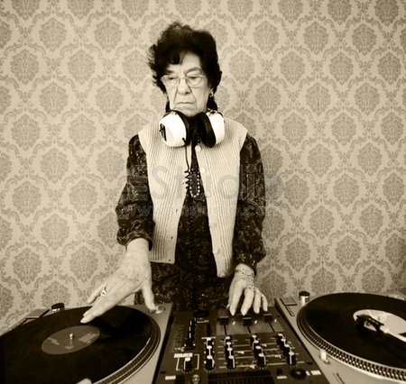 senior female dj mixes on her turntables