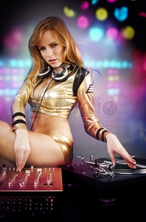 Beautiful DJ girl on decks on the party with the disco light on the background
