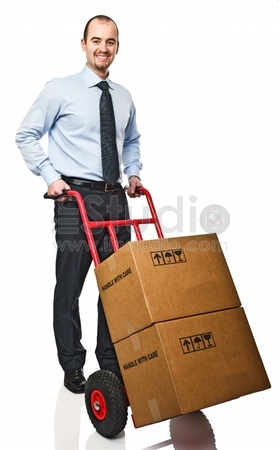 Smiling businessman with red handtruck and boxes