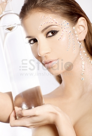 Picture of lovely woman in diamond make up with big bottle