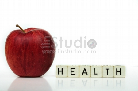 Red apple and cubes with letters in front of a white background - healthcare