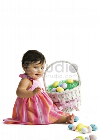 A biracial baby girl playing with her first Easter basket filled with eggs. Isolated on white.