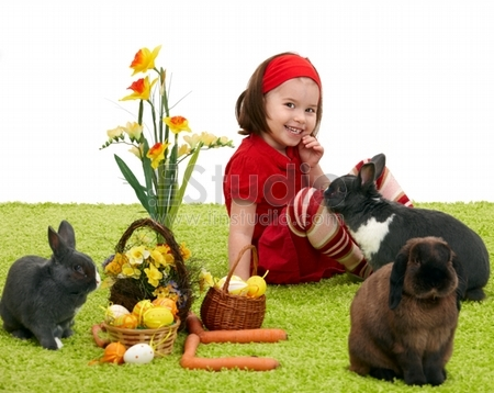 Easter image - smiling little girl with Easter bunny on green carpet
