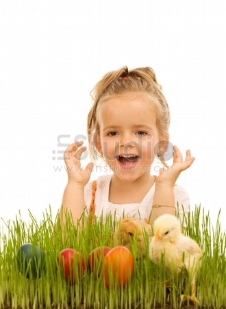 Happy little girl with easter eggs and baby chickens in the grass