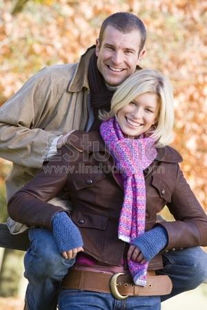 Couple on autumn walk sitting on fence