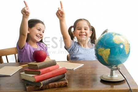 two girls pupels pointing in a class room with table, globe and red apple on a pile of books, Isolated on white