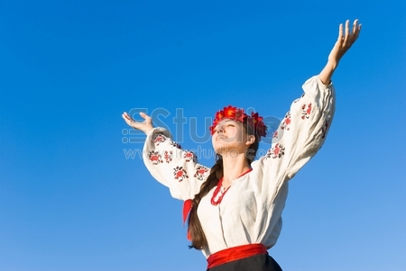 A Ukrainian woman in an authentic 19th century garment in the background of bright blue sky