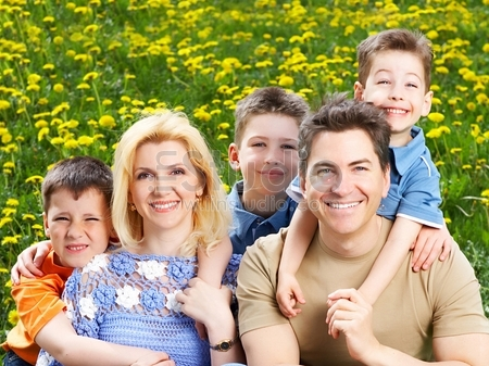Happy family- Father, mother and sons in the park