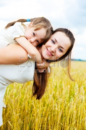 beautiful young mother and her daughter at the wheat field on a sunny day (focus on the child)