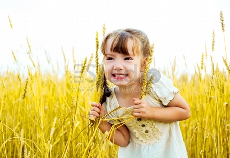 happy cute little girl in the wheat field on a warm summer day