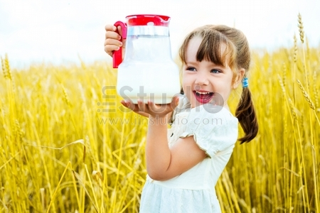 cute happy little girl in the wheat field holding a jug with milk