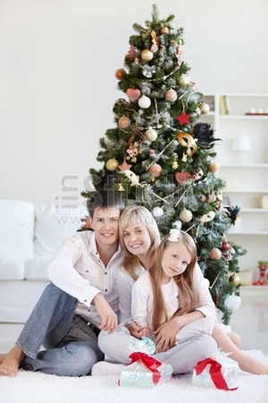A family with a daughter in the background of trees